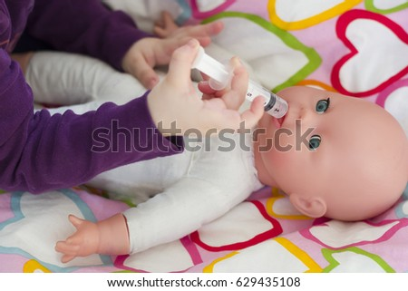 Little girl playing doctor with a doll and applying medicines with syringe and taking care of a doll, concept maternity, lifestyle and childhood