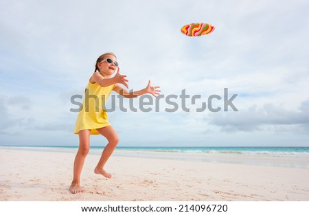 Little girl playing flying disk at beach during summer vacation