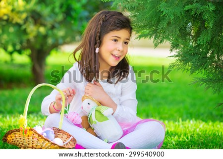 Little girl playing game outdoors with her rabbit toy, sweet adorable child finding colorful eggs, traditional Easter game - stock photo