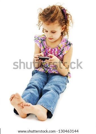 Little girl playing games in her cell phone. Isolated on a white background - stock photo