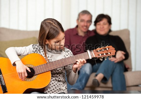 little girl playing guitar with her family at home - stock photo