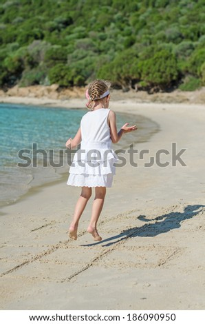 Little girl playing hopscotch game on the beach. - stock photo