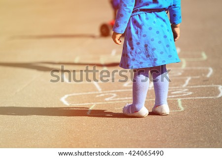 little girl playing hopscotch on playground - stock photo