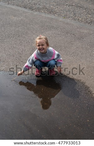 Little girl playing in a big puddle