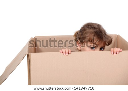 Little girl playing in a cardboard box - stock photo