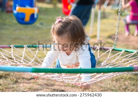 little girl playing in a park nest basket swing - stock photo