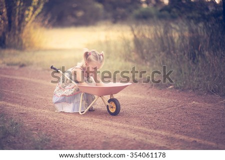 Little girl playing in a park with a wheelbarrow - stock photo