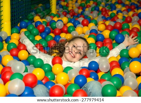 Little girl playing in colorful balls - stock photo