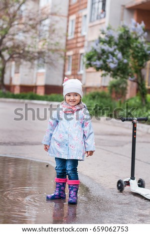 Little girl playing in muddy puddle on the road