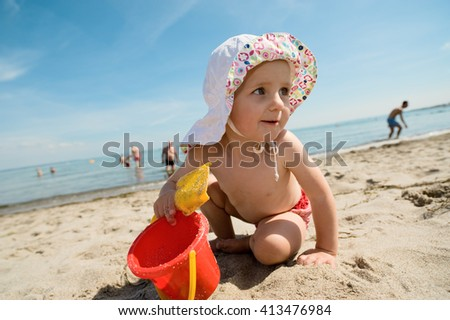 Little girl playing in sand at the Baltic Sea beach