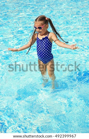 Little girl playing in swimming pool