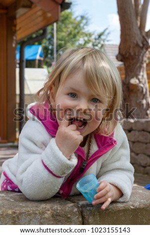 little girl playing in the home garden and eating some sand