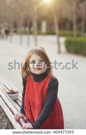 Little girl playing in the park. Portrait backlit. Beautiful litlle girl in red dress standing on the bench.