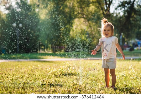 Little girl playing in the park with water drops - stock photo