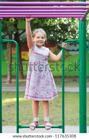 Little girl playing in the Playground in the yard