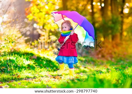 Little girl playing in the rain in autumn park. Child holding umbrella walking in the forest on a sunny fall day. Children playing outdoors with yellow maple leaf. Toddler girl picking golden leaves.  - stock photo
