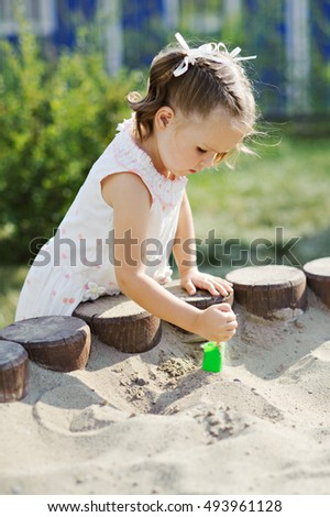 Little girl playing in the sandbox.