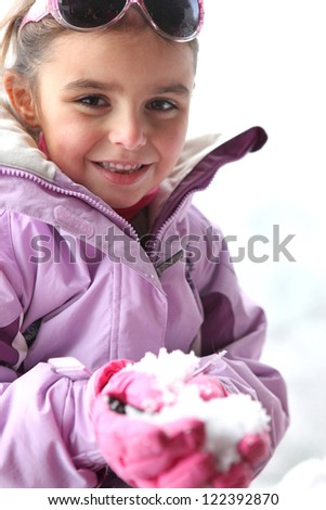 Little girl playing in the snow - stock photo