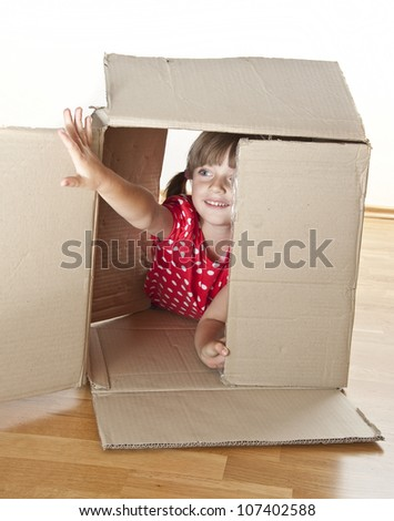 little girl playing inside a cardboard box