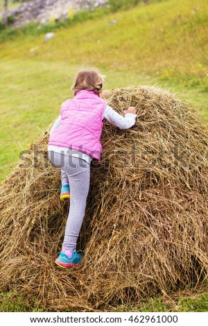 Little Girl playing on a haystack in a meadow, child outdoor activity.