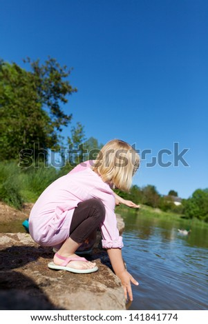 Little girl playing on a lake shore bending down trailing her hand in the calm water - stock photo