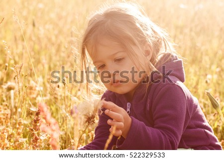 Little girl playing on meadow ,summer day in nature,