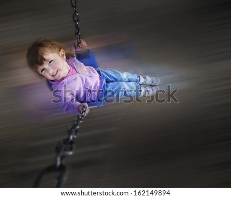 Little girl playing on merri-go-round at a park - stock photo