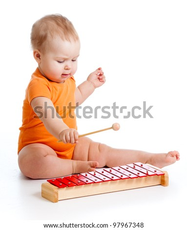 little girl playing on musical instrument - stock photo