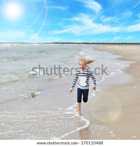 Little girl  playing on  sea beach - stock photo