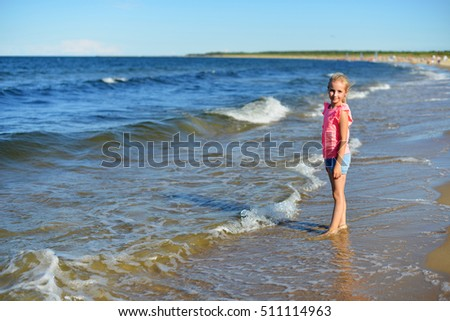 Little girl playing on sea beach