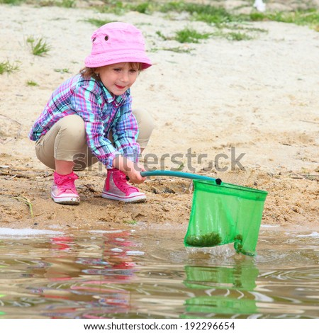Little girl playing on the beach. - stock photo