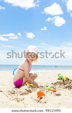 little girl playing on the beach at sea - stock photo