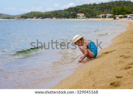 Little Girl Playing on the beach at the Aegean Sea. - stock photo