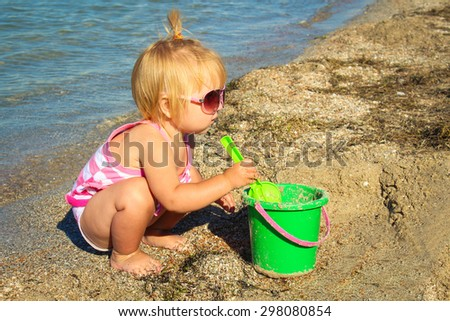 Little girl playing on the beach with pail and shovel. A child age 1 year builds sand pies. - stock photo