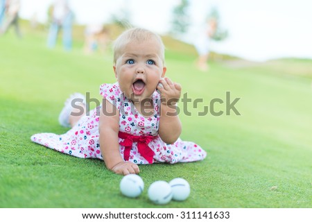 little girl playing on the lawn of golf balls and a stick