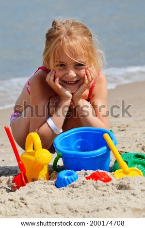 Little girl playing on the sand beach. Child and vacation.