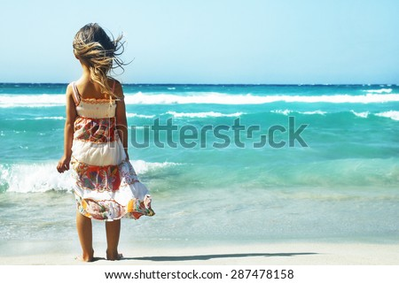little girl playing on the shore of the sea - stock photo