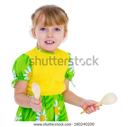 little girl playing on wooden spoons. Isolate on white background