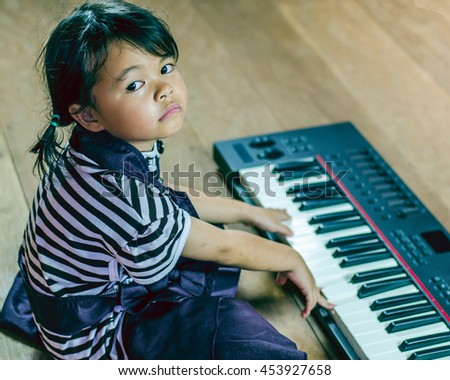 Little girl playing piano sitting on the floor