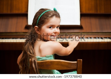 Little girl playing piano with sheet music. - stock photo