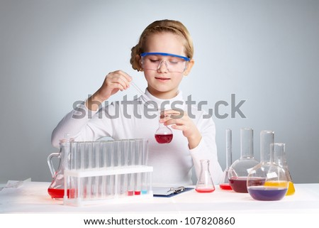 Little girl playing scientist pipetting fluid into a flask - stock photo