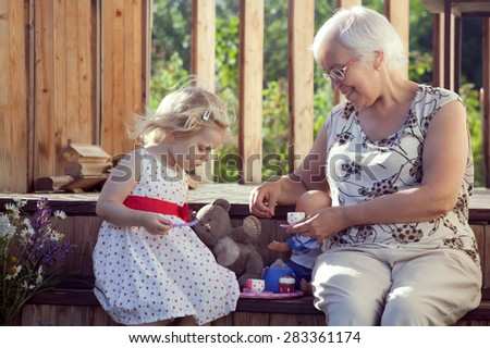 Little girl playing tea time with her grandmother on country house doorsteps in summer. Natural outdoor light setting. - stock photo