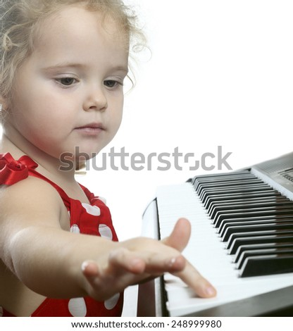 Little girl playing the piano. - stock photo