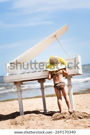 Little girl playing the piano at the beach. - stock photo
