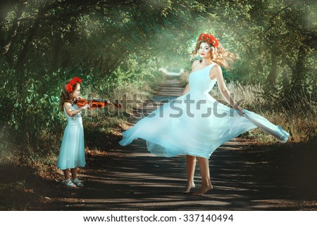 Little girl playing the violin, and an adult woman is dancing.  They are in the woods and are like at the fabulous fairies. - stock photo