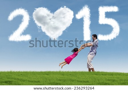 Little girl playing together with her father in meadow under cloud of 2015 - stock photo