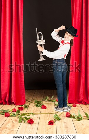 Little girl playing trumpet on stage theater - stock photo