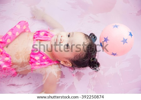 Little girl playing water in the pool, Selective Focus.