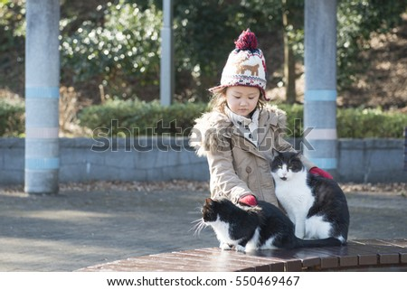 Little girl playing with a cat