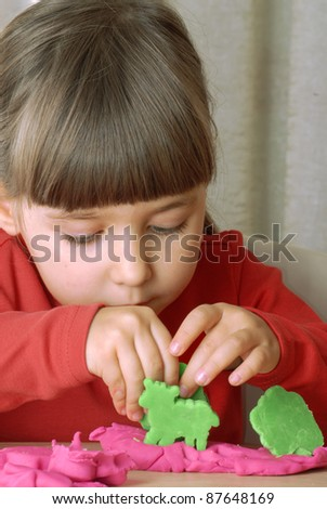 Little girl playing with a clay. - stock photo